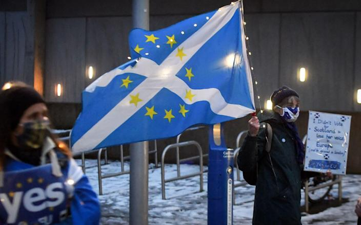 An anti-Brexit pro-Scottish independence activist holds a flag mixing the EU flag - ANDY BUCHANAN/AFP