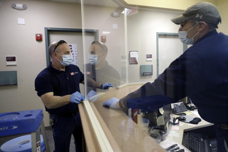 In this Wednesday, May 20, 2020 photo carpenters John Mackie, of Canton, Mass., left, and Doug Hathaway, of Holliston, Mass., right, apply trim to a newly installed plastic barrier in an office area, at Boston University, in Boston. Boston University is among a growing number of universities making plans to bring students back to campus this fall, but with new measures meant to keep the coronavirus at bay. (AP Photo/Steven Senne)