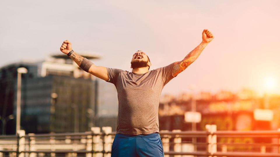 Male Runner Jogging in the city and finishing his training with his hands up in the air screaming with happiness.