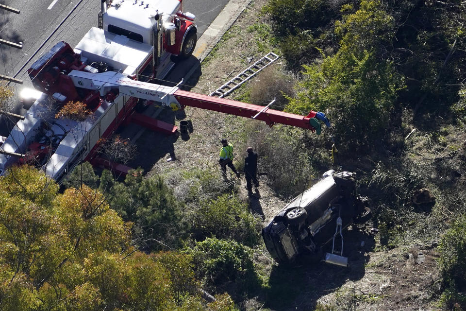"""A crane is used to lift a vehicle following a rollover accident involving golfer Tiger Woods in Rancho Palos Verdes, Calif., on Feb. 23, 2021.<span class=""""copyright"""">Mark J. Terrill—AP</span>"""