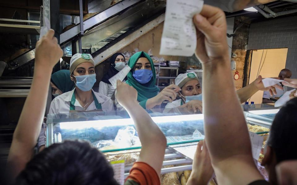 Workers wearing protective face masks serve a large crowd of customers at the counter inside a local bakery in Beirut as prices soar - Hasan Shaaban/Bloomberg