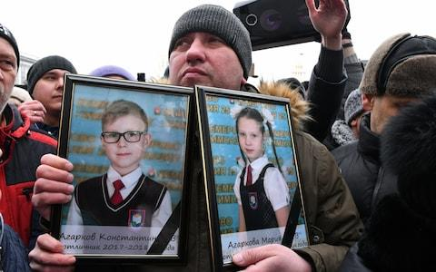Relatives held up pictures of children who had perished in the fire - Credit: TASS/Barcroft Images