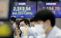 Currency traders watch computer monitors near the screens showing the Korea Composite Stock Price Index (KOSPI), left, and the foreign exchange rate between U.S. dollar and South Korean won at the foreign exchange dealing room in Seoul, South Korea, Thursday, Oct. 29, 2020. Asian shares logged moderate losses on Thursday and U.S. futures turned higher after the S&P 500 slid 3.5% overnight for its biggest drop since June. (AP Photo/Lee Jin-man)