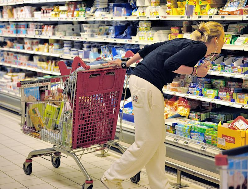 A woman looks at information on products as she buys groceries in an Auchan supermarket, a branch of the French international retail group Auchan, on June 27, 2014, in a Faches-Thumesnil shopping center, northern France