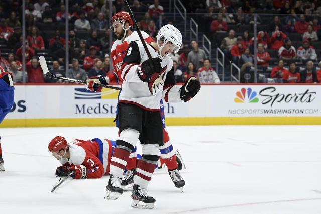 Arizona Coyotes center Clayton Keller (9) celebrates his goal past Washington Capitals right wing Tom Wilson, back, and defenseman Nick Jensen (3) during the first period of an NHL hockey game, Monday, Nov. 11, 2019, in Washington. (AP Photo/Nick Wass)