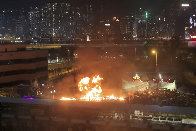 Protestors hurl molotov cocktails as armored police vehicles approach their barricades on a bridge over a highway leading to the Cross Harbour Tunnel in Hong Kong, Nov. 17, 2019. (Photo: Kin Cheung/AP)