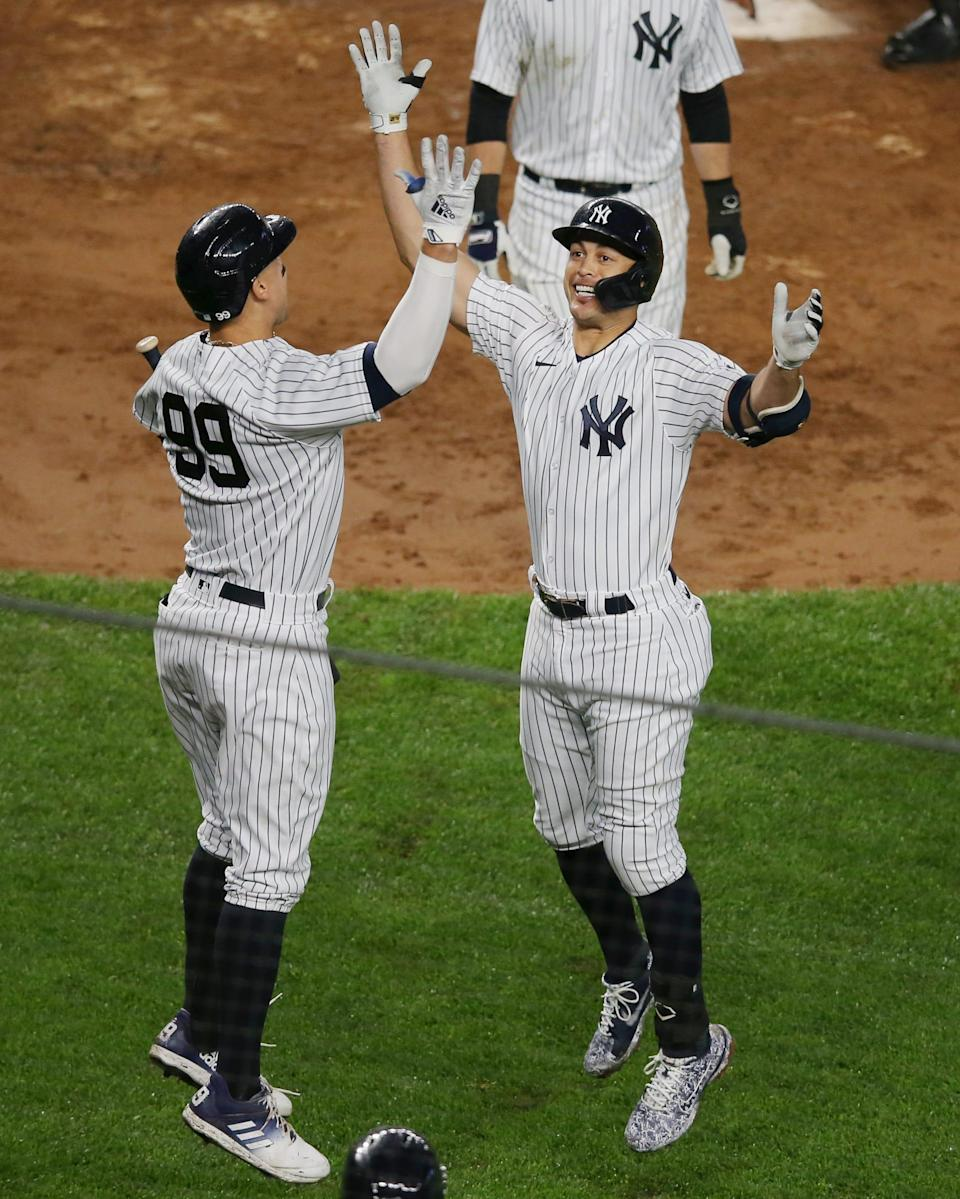 Giancarlo Stanton (right) celebrates his two-run home run against the Astros with teammate Aaron Judge.