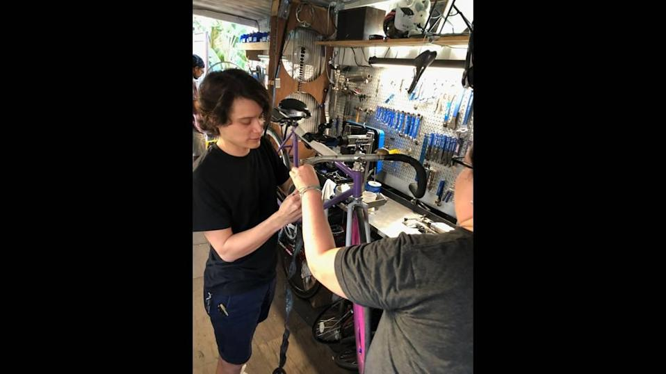 Magic City Bicycle Collective volunteer Marcelo Araica, left, installs bar tape on a bike for a customer. The collective is a nonprofit that accepts donations of new and used bicycles. Some bikes are sold to pay bills, and the rest are donated to those in need.