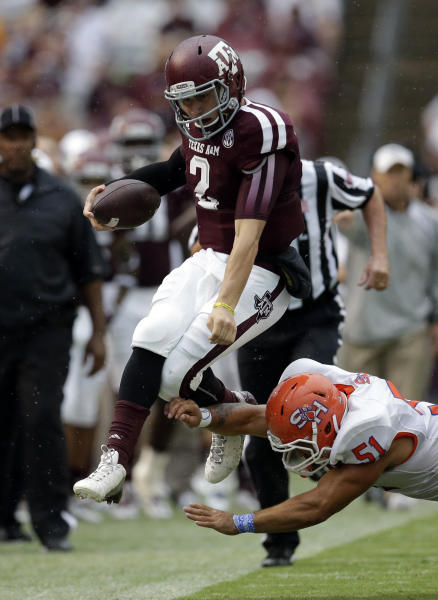 Texas A&M quarterback Johnny Manziel (2) leaps as Sam Houston State linebacker Eric Fieilo (51) hits him out of bounds during the first quarter of an NCAA college football game Saturday, Sept. 7, 2013, in College Station, Texas. (AP Photo/David J. Phillip)