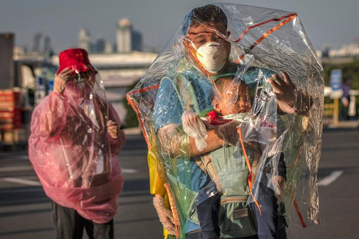 Travelers are seen wearing raincoats, plastic covers, gloves, goggles, and facemasks as they wait for their flight at Ninoy Aquino International Airport on March 18, 2020 in Manila, Philippines.