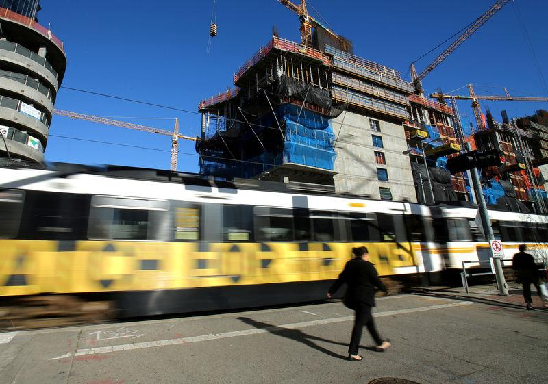 FILE PHOTO - A transit train passes a construction project in downtown Los Angeles, hangs from a building site in down town Los Angeles, California, U.S. on March 6, 2017. REUTERS/Mike Blake/File Photo