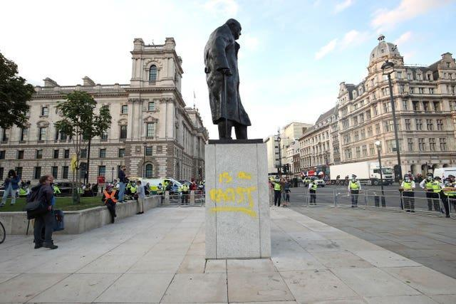 Police in a cordon around the statue of Winston Churchill, after it was vandalised