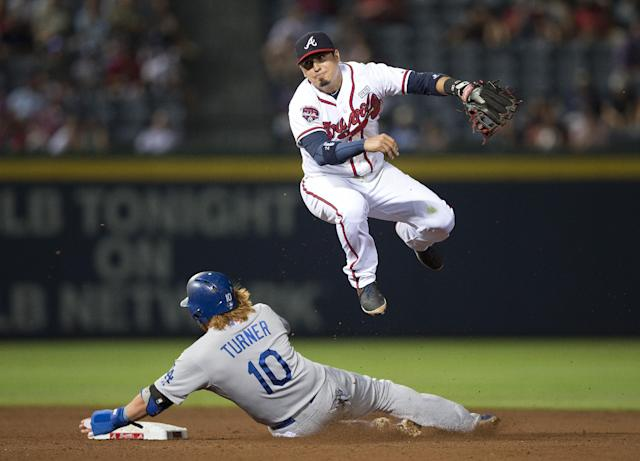 Atlanta Braves second baseman Ramiro Pena (14) avoids Los Angeles Dodgers' Justin Turner (10) as he tries to turn a double play on a A.J. Ellis ground ball in the eighth inning of a baseball game Monday, Aug. 11, 2014 in Atlanta. Ellis was safe at first allowing a run to score. (AP Photo/John Bazemore)