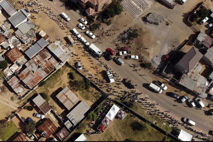 Thousands line up to receive food handouts in the Olievenhoutbos township of Midrand, South Africa, Saturday May 2, 2020. though South Africa begun a phased easing of its strict lockdown measures on May 1, its confirmed cases of coronavirus continue to increase. (AP Photo/Jerome Delay)