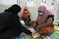 A volunteer teacher, left, gives a basic English lesson to a minority Muslim Rohingya refugees at a slum on the outskirts of Kuala Lumpur, Malaysia, on Oct. 11, 2020. Refugee women in Malaysia, some in their late 50s, are learning to read and write for the first time. The classes outside Kuala Lumpur are offered by the Women for Refugees group, which was formed in September by two law students to help illiterate migrant women integrate into the local community and empower them to be more than just passive wives. (AP Photo/Vincent Thian)