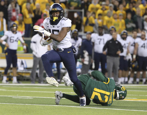 West Virginia wide receiver George Campbell (15) runs with a reception past Baylor cornerback Kalon Barnes (12) on the way to a touchdown during the second half of an NCAA college football game in Waco, Texas, Thursday, Oct. 31, 2019. (AP Photo/Jerry Larson)