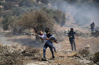 A Palestinian man carries a boy away from tear gas canisters fired by Israeli soldiers during a protest against the West Bank Jewish settlement outpost of Eviatar that was rapidly established the previous month, at the Palestinian village of Beita, near the West Bank city of Nablus, Friday, June 25, 2021. The Palestinians say it was established on their farmland and fear it will grow and merge with other large settlements in the area. (AP Photo/Majdi Mohammed)