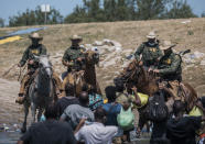 U.S. Customs and Border Protection mounted officers attempt to contain migrants as they cross the Rio Grande from Ciudad Acuña, Mexico, into Del Rio, Texas, Sunday, Sept. 19, 2021. Thousands of Haitian migrants have been arriving to Del Rio, Texas, as authorities attempt to close the border to stop the flow of migrants. (AP Photo/Felix Marquez)