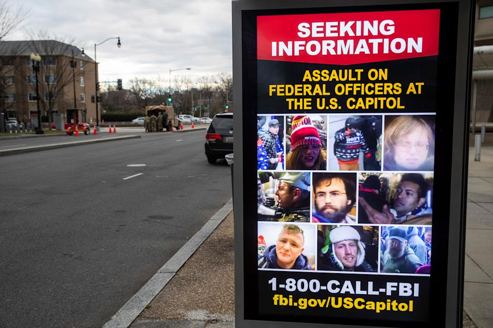 Wanted posters are displayed at a bus stop in a nearly deserted downtown as security perimeters expand ahead of the inauguration in Washington DC