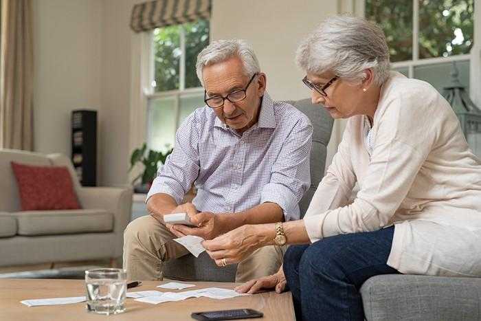 Older man and woman sitting on couch, looking at receipts