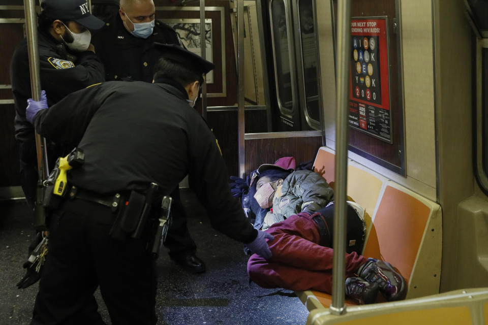 NYPD and MTA officers wake up a sleeping passenger before directing him to exit the 207th Street A-train station, Thursday, April 30, 2020, in the New York. (AP Photo/John Minchillo)