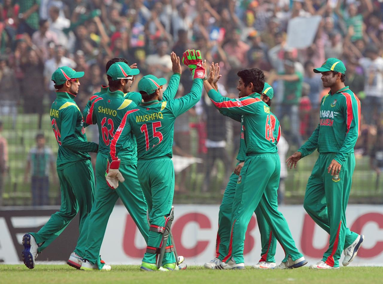 Bangladesh cricketers celebrate after the dismissal of the unseen New Zealand batsman Anton Devcich during the third One-Day International (ODI) cricket match between Bangladesh and New Zealand at Khan Jahan Ali Stadium in Fatullah on the outskirts of Dhaka on November 3, 2013 . AFP PHOTO/ Munir uz ZAMAN        (Photo credit should read MUNIR UZ ZAMAN/AFP/Getty Images)