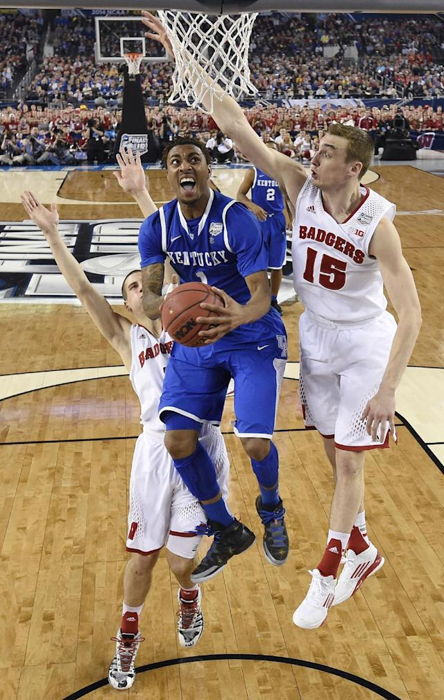 Kentucky guard James Young, center, drives to the basket between Wisconsin's Ben Brust, left, and Sam Dekker during the second half of an NCAA Final Four tournament college basketball semifinal game Saturday, April 5, 2014, in Arlington, Texas. (AP Photo/Chris Steppig, pool)