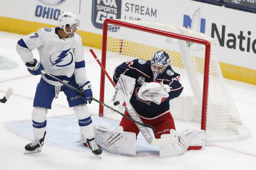 Columbus Blue Jackets' Elvis Merzlikins, right, of Latvia, makes a save as Tampa Bay Lightning's Mathieu Joseph looks on during the first period of an NHL hockey game Saturday, Jan. 23, 2021, in Columbus, Ohio. (AP Photo/Jay LaPrete)