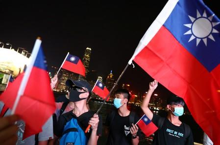 Anti-government protesters hold Taiwan national flags during a protest to celebrate Taiwan's National Day at the Harbour city in Tsim Sha Tsui district, in Hong Kong