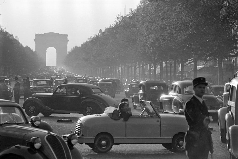 A traffic policeman directs traffic along the busy Champs-Élysées.