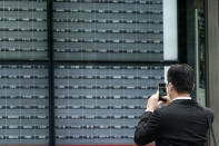 A man takes a photo of a blank electronic stock board supposedly showing Japan's Nikkei 225 index at a securities firm in Tokyo Thursday, Oct. 1, 2020. Trading on the Tokyo Stock Exchange was suspended Thursday because of a problem in the system for relaying market information. (AP Photo/Eugene Hoshiko)