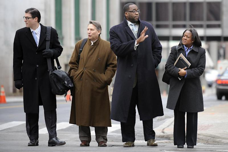 CORRECTS SPELLING OF DERRICK IN SECOND SENTENCE-- Kwame Kilpatrick, second from right, goes to federal court in Detroit on Monday Monday Jan. 7, 2013. Derick Miller, a longtime confidant of the former Detroit mayor, testified against Kilpatrick at his corruption trial Monday telling jurors he passed thousands of dollars to Kilpatrick from a contractor at the city's convention center. Kilpatrick resigned as mayor in 2008. Miller pleaded guilty to corruption in 2011 and agreed to cooperate with prosecutors. (AP Photo/Detroit News,David Coates ) DETROIT FREE PRESS OUT; HUFFINGTON POST OUT