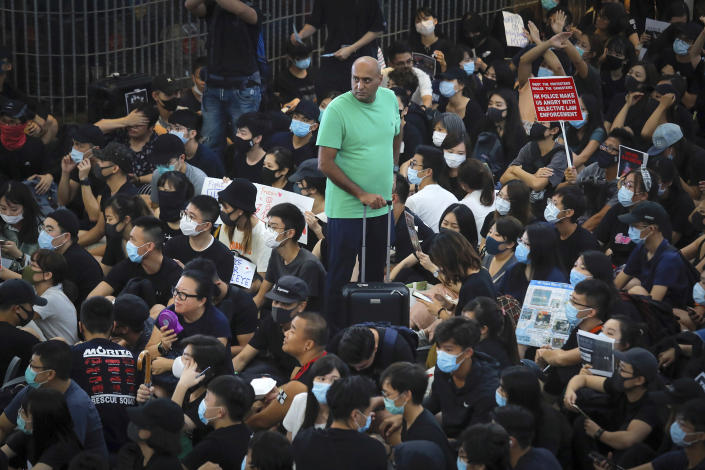 A traveler stands amidst protesters during a sit-in rally at the Airport in Hong Kong, Tuesday, Aug. 13, 2019. (Photo: Kin Cheung/AP)