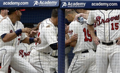 Atlanta Braves' Andrelton Simmons (19) is surrounded by teammates in the dugout after hitting his first major league career home run in the seventh inning of a baseball game against the Toronto Blue Jays, Saturday, June 9, 2012, in Atlanta. (AP Photo/David Goldman)