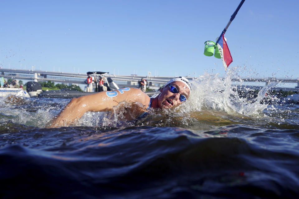 Gregorio Paltrinieri, of Italy, swims through a feeding station during the men's marathon swimming event at the 2020 Summer Olympics, Thursday, Aug. 5, 2021, in Tokyo. (AP Photo/David Goldman)
