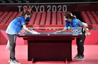 <p>Tokyo 2020 volunteers sanitise a table during a table tennis training session at the Tokyo Metropolitan Gymnasium, in Tokyo, on July 21, 2021, ahead of the Tokyo 2020 Olympic Games. (Photo by Jung Yeon-je / AFP) </p>