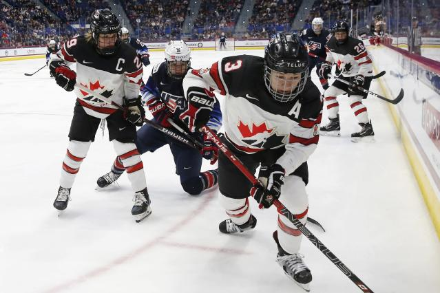 United States' Britta Curl (16) battles Canada's Jocelyne Larocque (3) and Marie-Philip Poulin (29) during the first period of a rivalry series women's hockey game in Hartford, Conn., Saturday, Dec. 14, 2019. (AP Photo/Michael Dwyer)