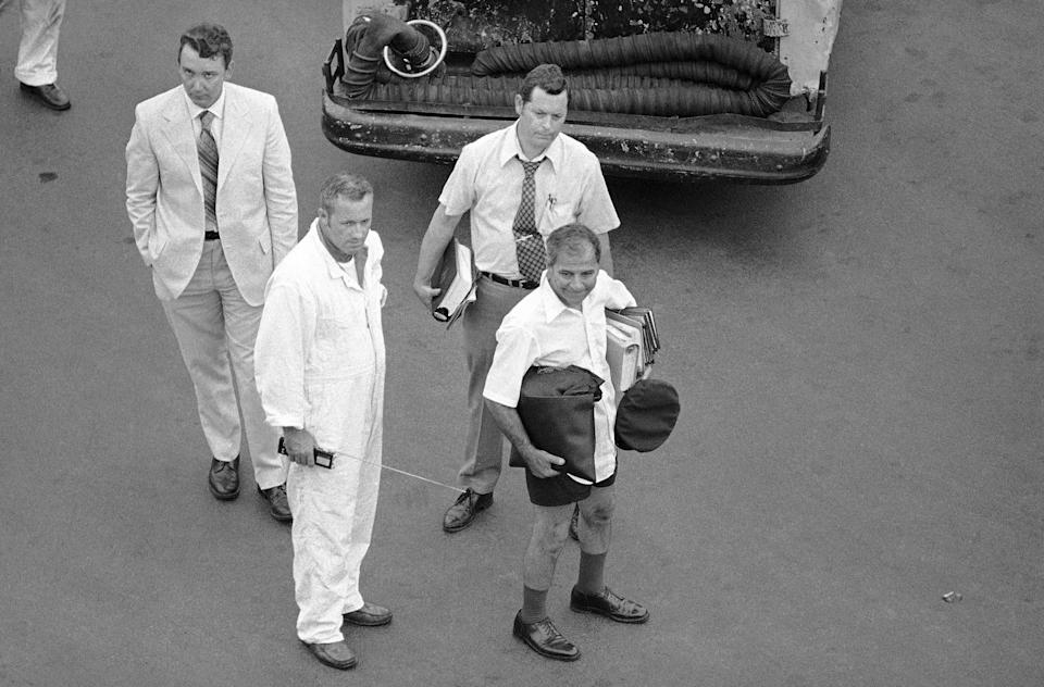 LEFT: An international navigator at Logan International Airport in Boston, clad in a bathing suit and carrying a briefcase of charts, gets ready to board the Delta Airlines plane hijacked by Melvin McNair and his associates on July 31, 1972.