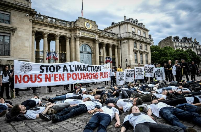 "Activists stage a ""die-in"" on June 4, 2019 to denounce the air quality outside the French National Assembly in Paris (AFP Photo/STEPHANE DE SAKUTIN)"