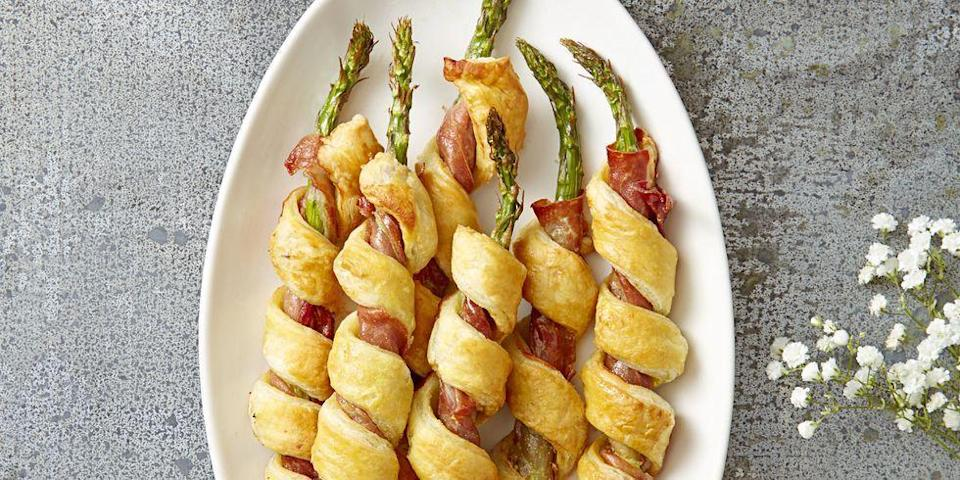 """<p>This asparagus and prosciutto recipe is an elevated take on the classic pigs in a blanket. </p><p><em><a href=""""https://www.goodhousekeeping.com/food-recipes/a38354/sprigs-in-a-blanket-recipe/"""" rel=""""nofollow noopener"""" target=""""_blank"""" data-ylk=""""slk:Get the recipe for Sprigs in a Blanket »"""" class=""""link rapid-noclick-resp"""">Get the recipe for Sprigs in a Blanket »</a></em></p>"""