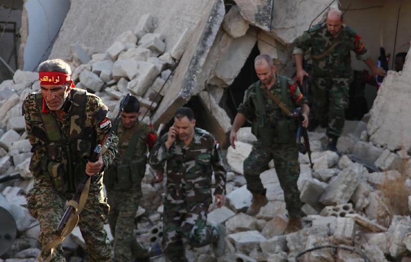 Syrian pro-government soldiers patrol the Uwaija neighborhood as they advance in Aleppo's rebel-held areas (AFP Photo/George Ourfalian)