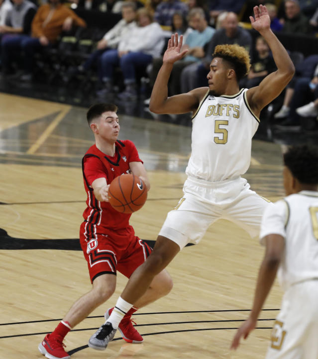 Utah guard Rylan Jones, left, passes the ball under defensive pressure from Colorado guard D'Shawn Schwartz in the first half of an NCAA college basketball game Sunday, Jan. 12, 2020, in Boulder, Colo. (AP Photo/David Zalubowski)