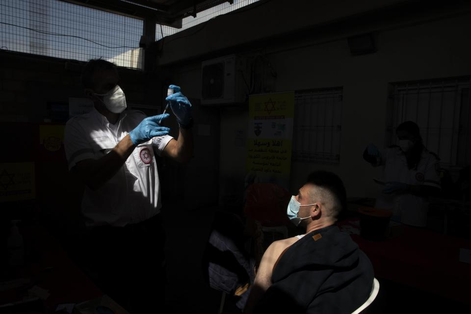 A Palestinian worker who works in Israel receives a Moderna COVID-19 vaccine at the Tarkumiya crossing between the West Bank and Israel, Monday, March 8, 2021. (AP Photo/Sebastian Scheiner)