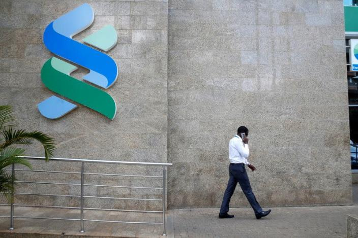 FILE PHOTO: A man walks past a logo of the Standard Chartered Kenya bank in their main office in Nairobi,