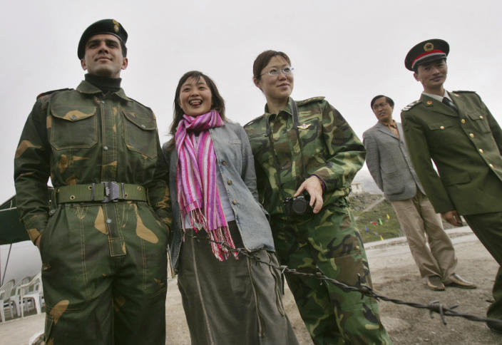 FILE - In this July 5, 2006 file photo, Indian army Capt. Nitesh Sharma, left, poses with Chinese civilian Chen Xiao, second left, and a Chinese soldier, third right, on the international border at the Nathu La Pass, in northeastern Indian state of Sikkim. While the recent troop standoff in a remote Himalayan desert spotlights a long-running border dispute between China and India, the two emerging giants are engaged in a rivalry for global influence that spreads much farther afield. (AP Photo/Gurinder Osan, File)