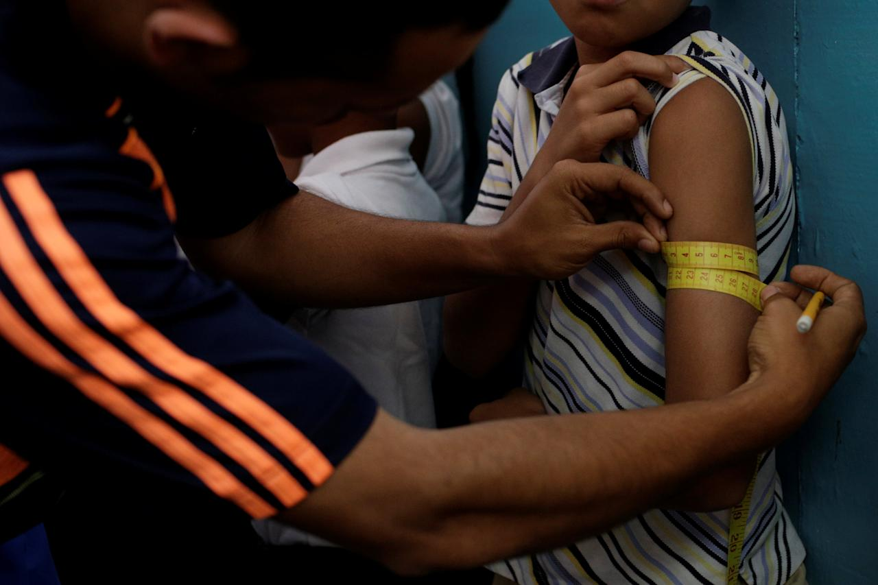 A teacher measures a child's arm as part of a health program of the Miranda state government at a school in Caracas, Venezuela March 25, 2017. Picture taken March 25, 2017. REUTERS/Marco Bello