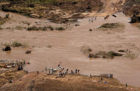 FILE PHOTO: People stand on the banks where the bridge was washed away, in the aftermath of Cyclone Idai, near the village of John Segredo