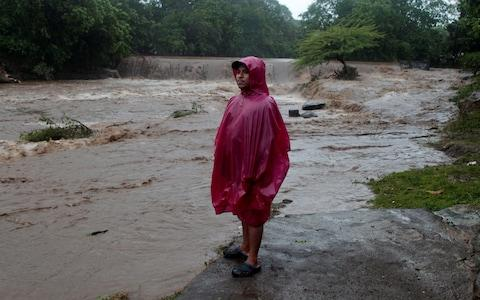 A resident stands on the shore of the Masachapa river, flooded by heavy rains by Tropical Storm Nate in the outskirts of Managua, Nicaragua - Credit: Reuters