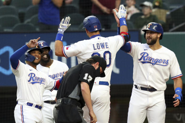 Texas Rangers' Nate Lowe (30) is greeted by Willie Calhoun (5), Adolis Garcia (53) and Joey Gallo (13) after hitting a three-run home run against the Los Angeles Angels in the first inning of a baseball game Monday, April 26, 2021, in Arlington, Texas. (AP Photo/Richard W. Rodriguez)