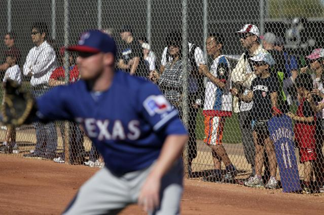 Texas Rangers pitcher Robbie Ross waits for a throw during warm ups as fans line the fence watching the team during spring training baseball practice, Monday, Feb. 17, 2014, in Surprise, Ariz. (AP Photo/Tony Gutierrez)